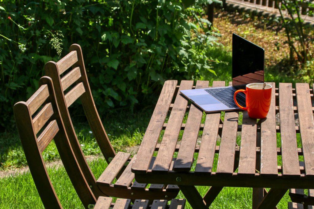 Garttisch, der mit einem Laptop und einer Tasse darauf im Grünen steht.